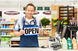 Smiling man holding an open sign inside a store