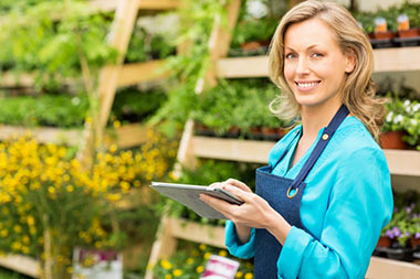 Smiling woman holding a tablet in front of shelves filled with flowers and plants