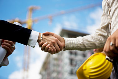 Close up of a professional and construction worker shaking hands