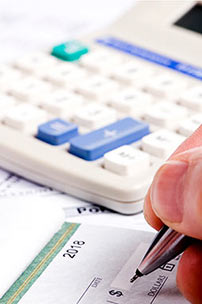 Close up of pen about to write something on a check with a calculator in the background