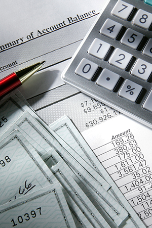A pen, calculator and checks placed on a financial balance sheet