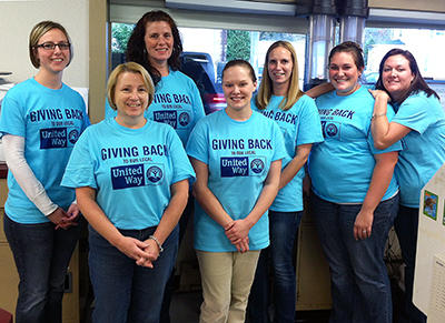 Seven women bank representatives wearing shirts saying Giving Back to the United Way