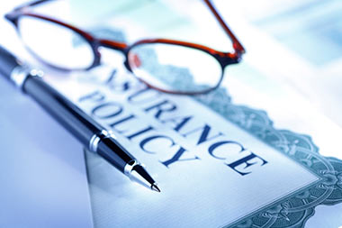 Glasses and a pen placed on an insurance policy