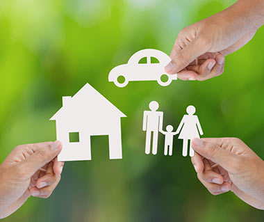 Close up of hands holding paper cut outs of a car, house and family