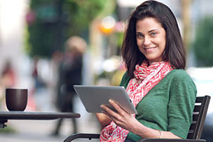 A smiling woman sitting at an outdoor cafe holding a tablet