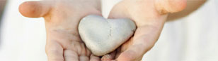 Two hands presenting a heart shaped stone
